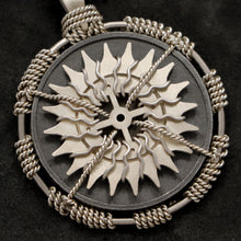 Load image into Gallery viewer, Detail view of 18K Palladium White Gold and Sterling Silver Sewn Gold Metal Compass pendant featuring 20 pointed gear by Caps Brothers