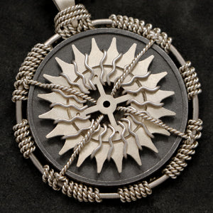 Detail view of 18K Palladium White Gold and Sterling Silver Sewn Gold Metal Compass pendant featuring 20 pointed gear by Caps Brothers