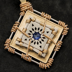 Detail view of 18K Yellow Gold and 18K Palladium White Gold and Sapphire Sewn Gold Metal Confidence pendant featuring 4 pointed gear by Caps Brothers