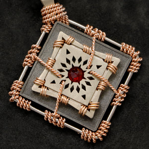 Detail view of 18K Rose Gold and 18K Palladium White Gold and Sterling Silver and Ruby Sewn Gold Metal Confidence pendant featuring 4 pointed gear by Caps Brothers