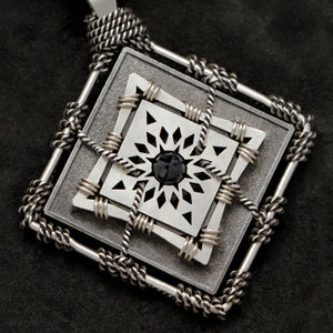 Detail view of Sterling Silver and 18K Palladium White Gold Accents and Black Sapphire Sewn Silver Metal Confidence pendant featuring 4 pointed gear by Caps Brothers
