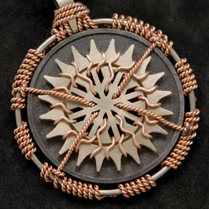 Detail view of 18K Rose Gold and 18K Palladium White Gold and Sterling Silver Sewn Silver Metal Sun pendant featuring 20 pointed gear by Caps Brothers