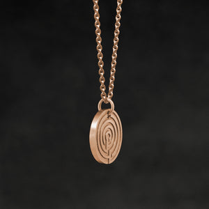 Side view of 18K Rose Gold Journey pendant and chain necklace featuring labyrinth as inward journey by Caps Brothers