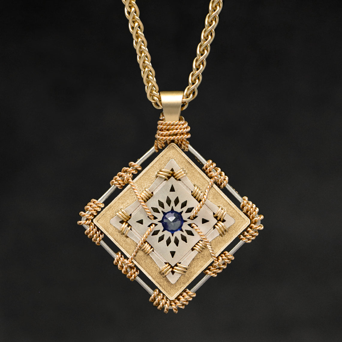 Hanging front view of 18K Yellow Gold and 18K Palladium White Gold and Sapphire Sewn Gold Metal Confidence pendant and chain with endless loop necklace featuring 4 pointed gear by Caps Brothers