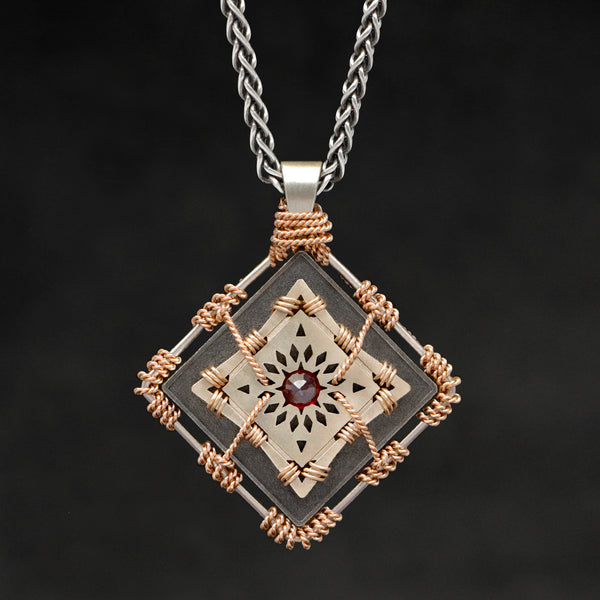 Hanging front view of 18K Rose Gold and 18K Palladium White Gold and Sterling Silver and Ruby Sewn Gold Metal Confidence pendant and chain with endless loop necklace featuring 4 pointed gear by Caps Brothers
