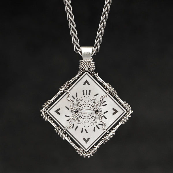 Hanging reverse view of Sterling Silver and 18K Palladium White Gold Accents Sewn Silver Metal Confidence pendant and chain with endless loop necklace featuring Electromagnetic Field and Cardinal Directions by Caps Brothers