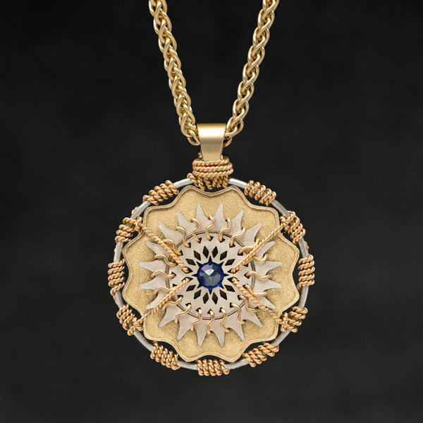 Hanging front view of 18K Yellow Gold and 18K Palladium White Gold and Sapphire Sewn Gold Metal Majesty pendant and chain with endless loop necklace featuring 20 pointed gear by Caps Brothers