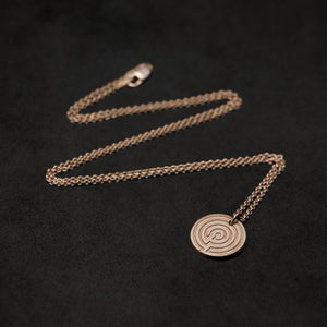 Laying down 18K Rose Gold Journey pendant and chain necklace with clasp featuring labyrinth as inward journey by Caps Brothers