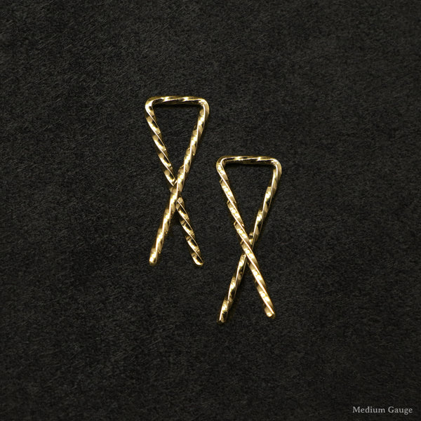 Laying down pair of 18K Yellow Gold Sibling Ribbons Twisted Earrings representing we are all brothers and sisters by Caps Brothers