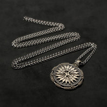 Load image into Gallery viewer, Laying down view of 18K Palladium White Gold and Sterling Silver Sewn Gold Metal Compass pendant and chain with endless loop necklace featuring 20 pointed gear by Caps Brothers