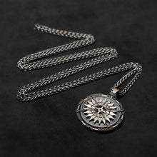 Load image into Gallery viewer, Laying down view of Sterling Silver and 18K Palladium White Gold Accents Sewn Silver Metal Compass pendant and chain with endless loop necklace featuring 20 pointed gear by Caps Brothers