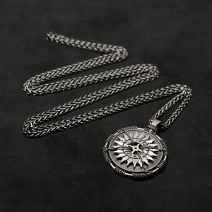 Laying down view of Sterling Silver and 18K Palladium White Gold Accents Sewn Silver Metal Compass pendant and chain with endless loop necklace featuring 20 pointed gear by Caps Brothers