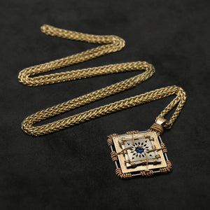 Laying down view of 18K Yellow Gold and 18K Palladium White Gold and Sapphire Sewn Gold Metal Confidence pendant and chain with endless loop necklace featuring 4 pointed gear by Caps Brothers