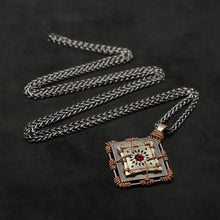 Load image into Gallery viewer, Laying down view of 18K Rose Gold and 18K Palladium White Gold and Sterling Silver and Ruby Sewn Gold Metal Confidence pendant and chain with endless loop necklace featuring 4 pointed gear by Caps Brothers