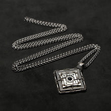 Load image into Gallery viewer, Laying down view of Sterling Silver and 18K Palladium White Gold Accents and Black Sapphire Sewn Silver Metal Confidence pendant and chain with endless loop necklace featuring 4 pointed gear by Caps Brothers