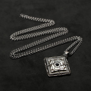 Laying down view of Sterling Silver and 18K Palladium White Gold Accents and Black Sapphire Sewn Silver Metal Confidence pendant and chain with endless loop necklace featuring 4 pointed gear by Caps Brothers