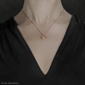 Closeup of model wearing 18K Rose Gold Journey pendant and chain necklace featuring the Map of Humanity as outward journey by Caps Brothers