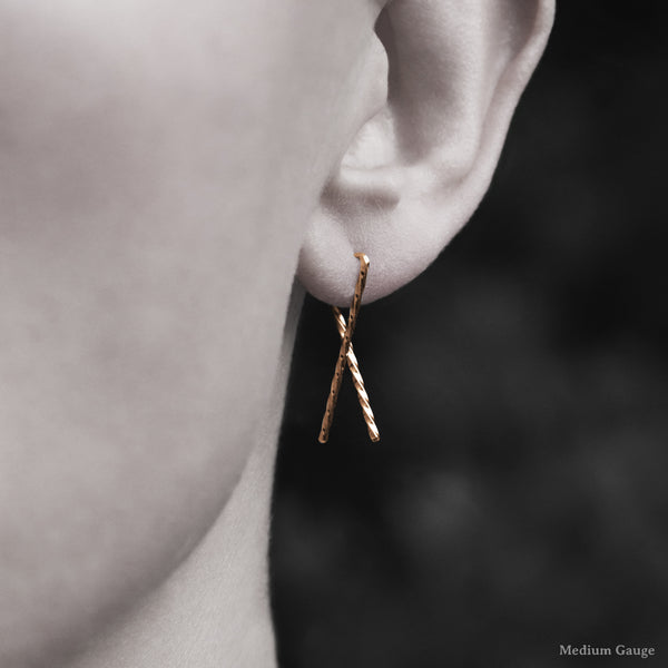 Model wearing 18K Rose Gold Sibling Ribbon Twisted Earring representing we are all brothers and sisters by Caps Brothers