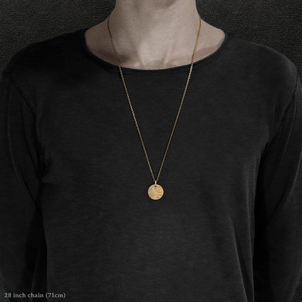 Model wearing 18K Yellow Gold Journey pendant and chain with endless loop necklace featuring the Map of Humanity as outward journey by Caps Brothers