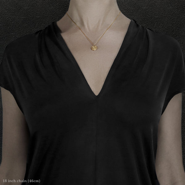 Model wearing 18K Yellow Gold Journey pendant and chain necklace featuring the Map of Humanity as outward journey by Caps Brothers