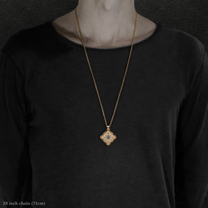 Model wearing 18K Yellow Gold and 18K Palladium White Gold and Sapphire Sewn Gold Metal Confidence pendant and chain with endless loop necklace featuring 4 pointed gear by Caps Brothers