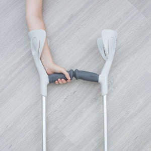 Hand on crutches with black sleeve