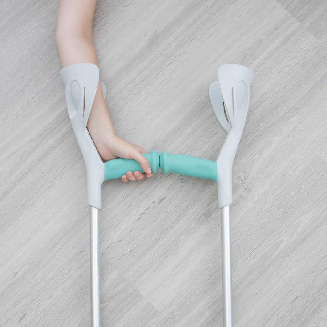 Hand on crutches with turquoise sleeve