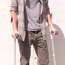 Load image into Gallery viewer, man holding black crutches