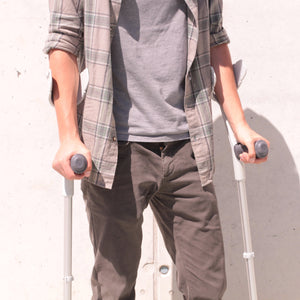 man holding black crutches