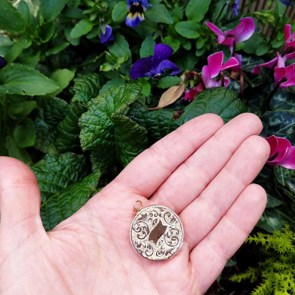 antique locket in hand for scale