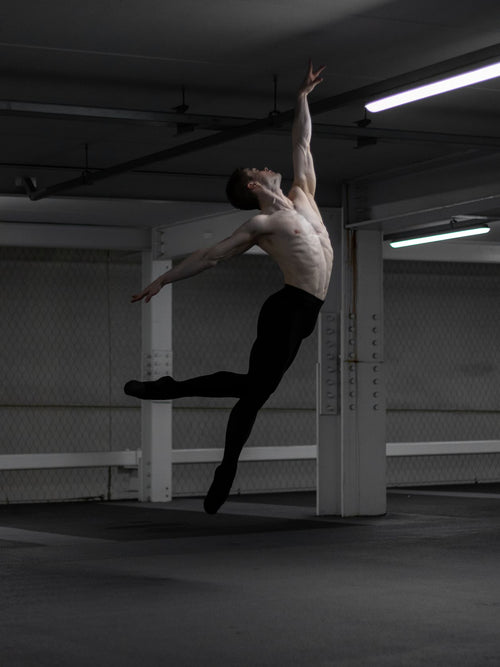 male ballet dancer jumping in the air inside an underground dimly lit car park