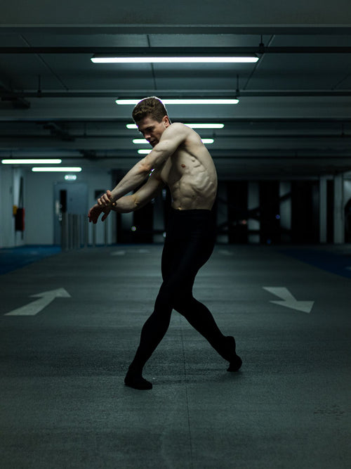Male ballet dancer in a pose wearing black tights and bare torso in an underground carpark