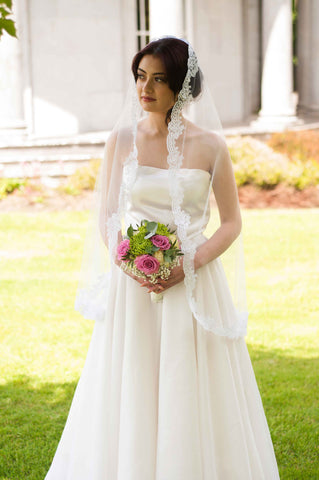 Bride looking up to a tree while standing on a lawn and holding a pink and green bouquet