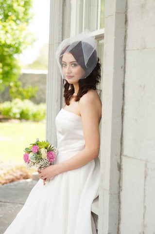 Bride leaning again windowsill wearing a tulle birdcage veil