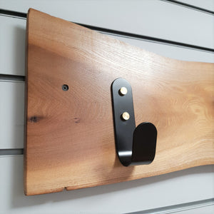 Wooden coat rack with black hooks