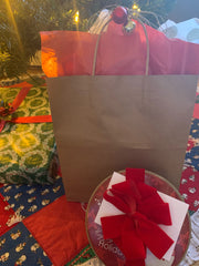 Gifts wrapped in a repurposed brown bag, with repurposed ornaments on the handle, and a repurposed cookie tin with reused ribbon wrapped around it.