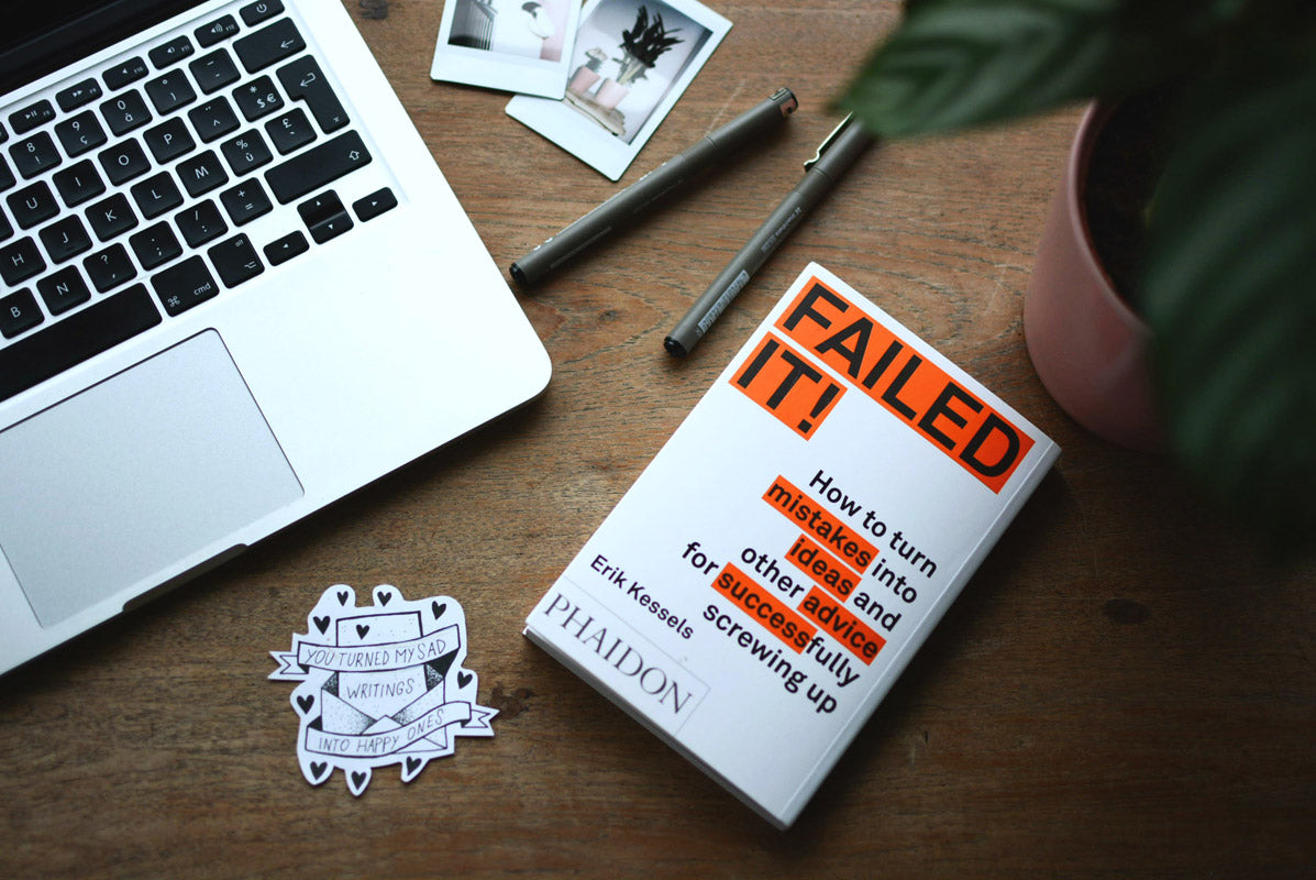 Image of a book, laptop and sticker on a desk