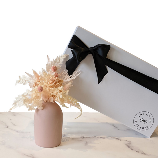 Dried flower bouquet featuring peach, cream and pink steams in a blush pink vase with a premium matt white gift box and black satin ribbon