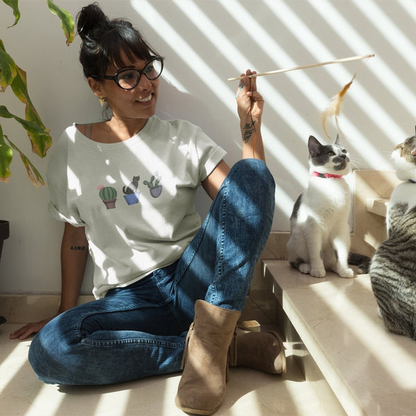 woman wearing cat cactus tshirt while playing with cats on stairs next to plant