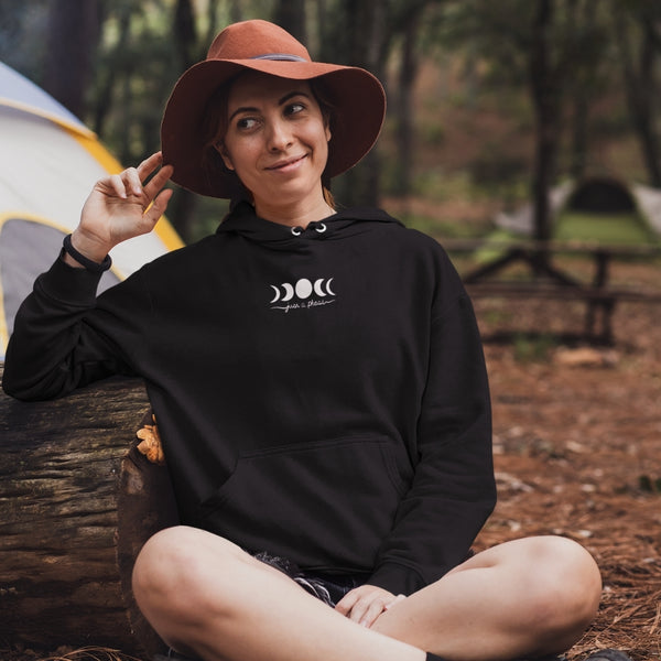 woman wearing just a moon phase hoodie with hat in the woods