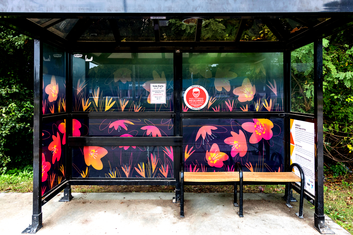 pink and orange flower art on a black framed bus stop with bench