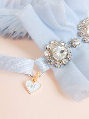 Close up detail of Alexandra silk chiffon wedding garter with rhinestone banding and gold plated mamie + james charm