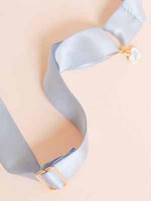 Mamie and James detail image of Amelie adjustable silk bow wedding garter in french blue with rhinestone appliqué in gold tone setting