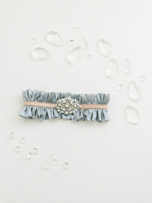 Mamie + James Charlotte silk charmeuse adjustable wedding garter with nude stretch banding and Antoinette blue silk charmeuse with rhinestone appliqué in a silver tone setting