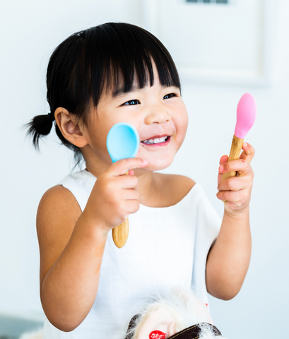 child with pink and blue spoon