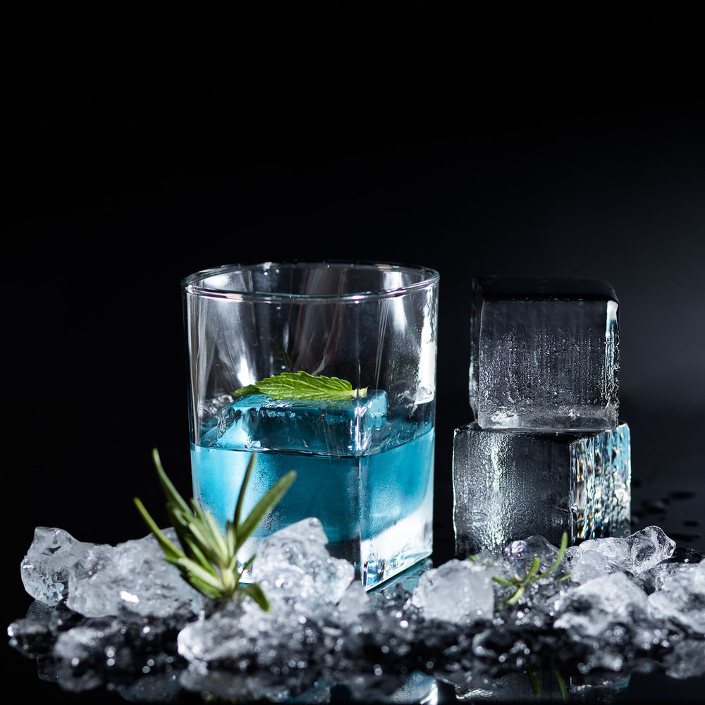 "A blue cocktail served with a 2"" Custom Cocktail Cube"