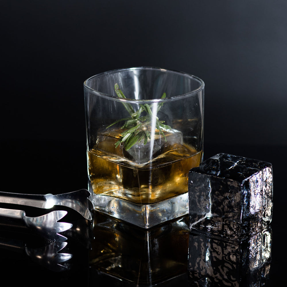 "2"" Custom Ice Cube served with Whiskey and a garnish. With a pair of ice tongs and ice cube on the side."