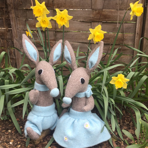 Boy and girl bunny rabbits with daffodils