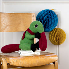 duck billed platypus  soft toy in green and red on a chair