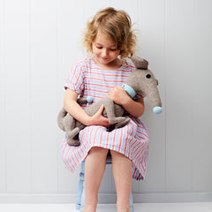 Dachshund in grey with blue collar sitting with a little girl looking down